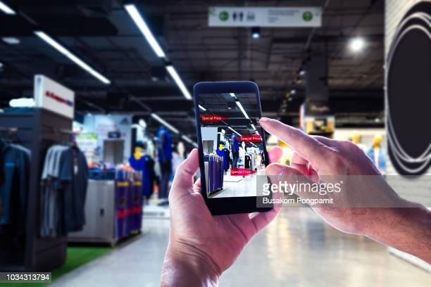 augmented reality marketing concept. hand holding digital tablet smart phone use ar application to check special sale price in retail fashion shop mall - stereoscopic images stock photos and pictures