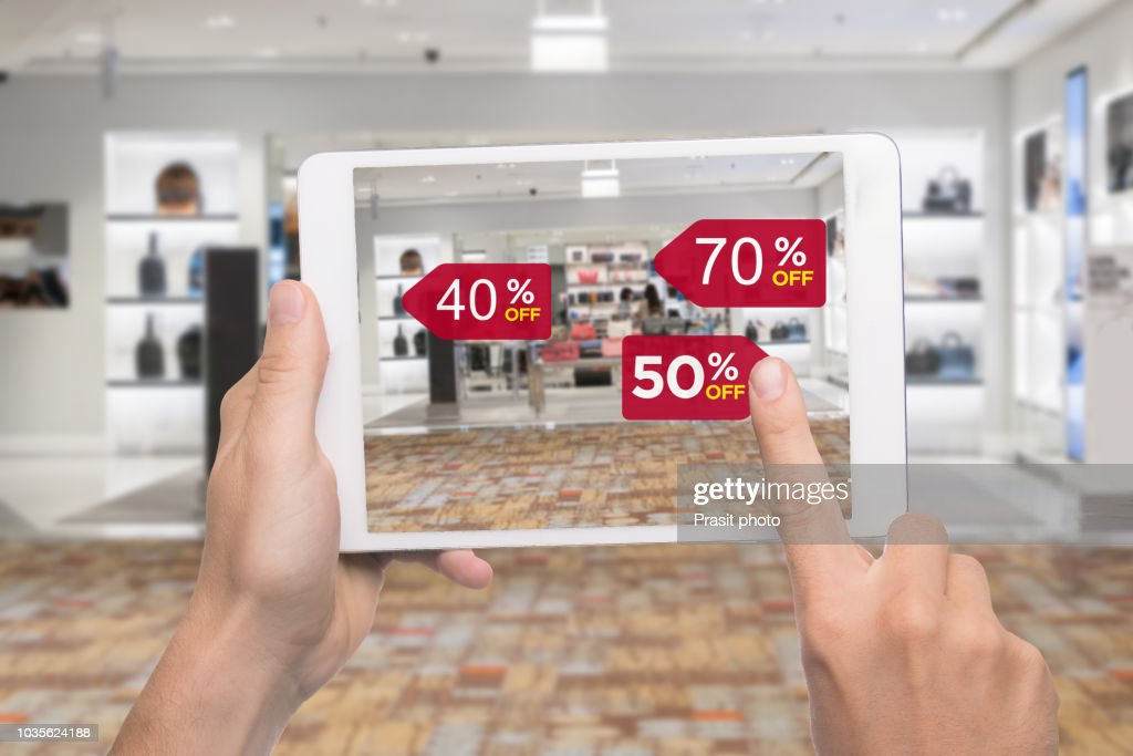 Augmented reality marketing concept. Hand holding digital tablet smart phone use AR application to check special sale price in retail fashion shop mall : Stock Photo