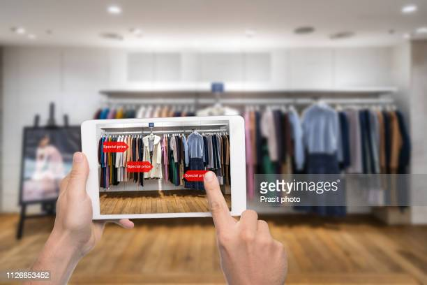 augmented reality marketing concept. hand holding digital tablet smart phone use ar application to check special sale price in retail fashion shop mall - realtà aumentata foto e immagini stock