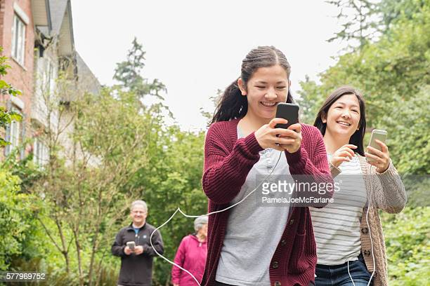 Augmented Reality Mobile Phone Gamers, Young Women Running with Smartphones