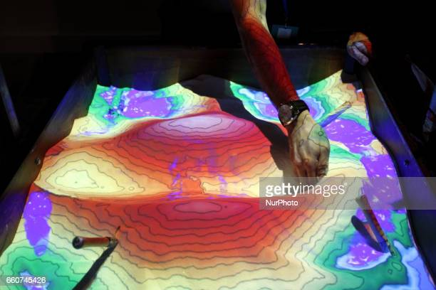 Augmented reality sandbox allows users to create topography models by shaping real sand which is then augmented in real time by an elevation colour...
