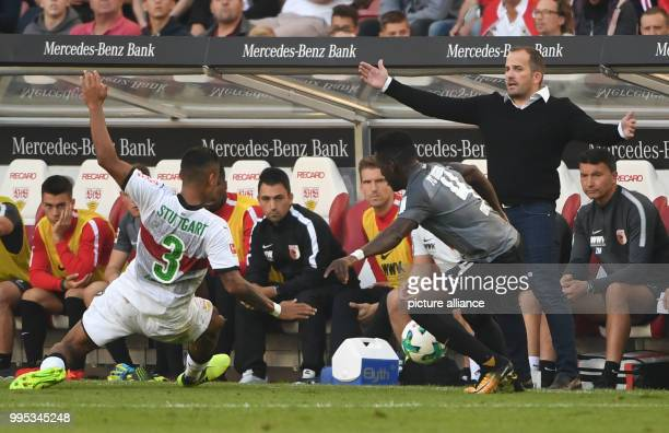 Augsburg coach Manuel Baum reacts as Augsburg's Daniel Tawiah Opare and Stuttgart's Dennis Aogo vie for the ball during the German Bundesliga match...