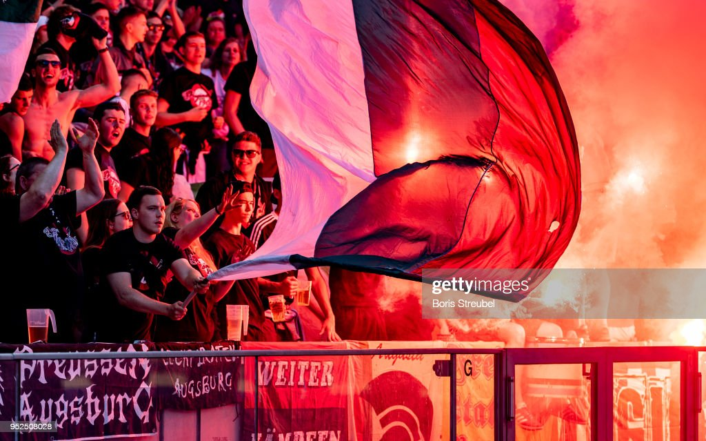Augsburg fans burn flares during the Bundesliga match between Hertha BSC and FC Augsburg at Olympiastadion on April 28, 2018 in Berlin, Germany.