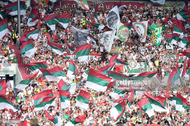 Augsburg supporters wave flags during the Bundesliga match between FC Augsburg and Borussia Moenchengladbach at WWKArena on August 26 2017 in...