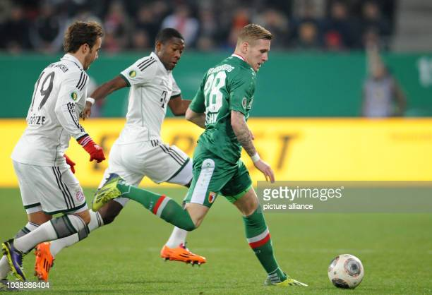 Augsburg's Andre Hahn vies for the ball with Munich's Mario Goetze and David Alaba celebrate after Robben's 10 goal during the DFB cup round of...