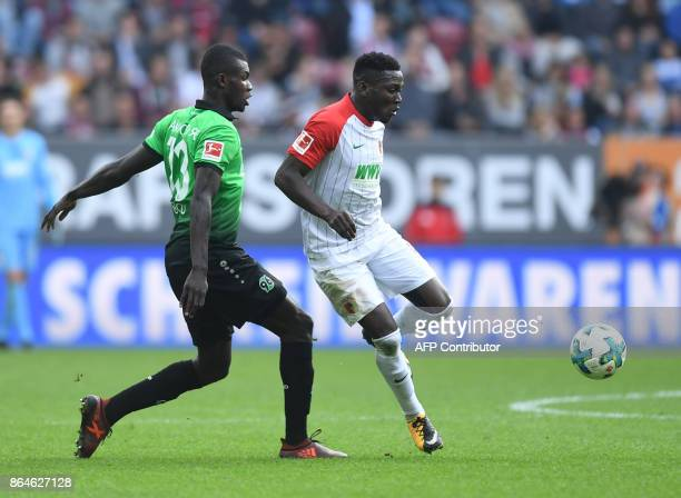 Augsburg's Austrian defender Kevin Danso vies with Hanover's Togolese striker Ihlas Bebou during the German first division Bundesliga football match...