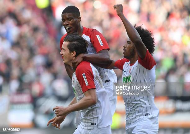Augsburg's Austrian midfielder Michael Gregoritsch defender Kevin Danso and Brazilian midfielder Caiuby celebrate after scoring their first goal...