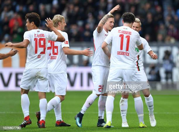 Augsburg's Austrian midfielder Michael Gregoritsch is congratulated by teammates Augsburg's South Korean midfielder Koo Jacheol Augsburg's Austrian...