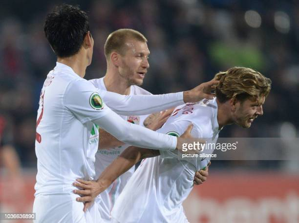Augsburg's DongWon Ji Ragnar Klavan and Alexander Esswein celebrate the 20 goal during the DFB Cup match between SC Freiburg and FC Augsburg in the...