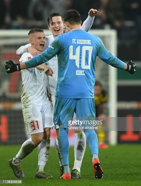Augsburg's German defender Philipp Max, Augsburg's Austrian midfielder Michael Gregoritsch and Augsburg's Swiss goalkeeper Gregor Kobel react after...