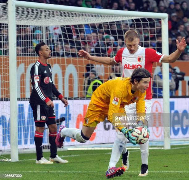 Augsburg's goalkeeper Marwin Hitz and Ragnar Klavan fight for the ball against Leverkusen's Karim Bellarabi during the German Bundesliga soccer match...