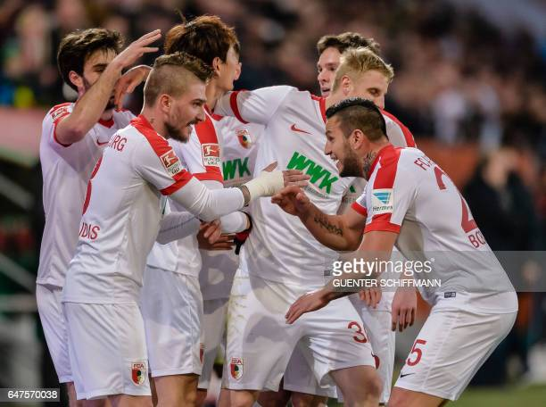 Augsburg's Greek defender Konstantinos Stafylidis celebrates scoring the opening goal with his teammates during the German first division Bundesliga...