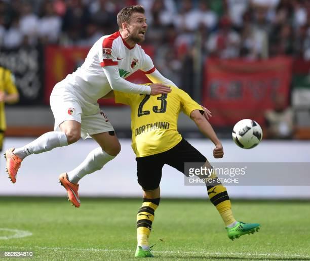 Augsburg's midfielder Daniel Baier and Dortmund's Japanese midfielder Shinji Kagawa vie for the ball during the German first division Bundesliga...
