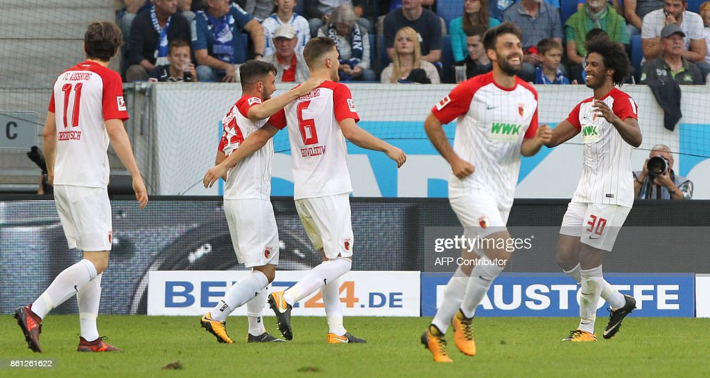 Augsburg's players celebrate the 2-2 own goal during the German First division Bundesliga football match TSG 1899 Hoffenheim vs FC Augsburg in Sinsheim, southwestern Germany, on October 14, 2017. / AFP PHOTO / Amelie
