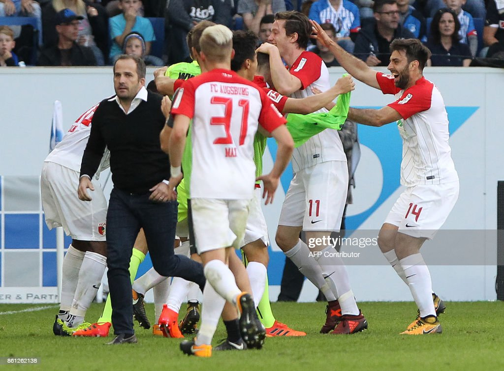 Augsburg's players celebrate with their head coach Manuel Baum (L) the 2-2 own goal during the German First division Bundesliga football match TSG 1899 Hoffenheim vs FC Augsburg in Sinsheim, southwestern Germany, on October 14, 2017. / AFP PHOTO / Amelie