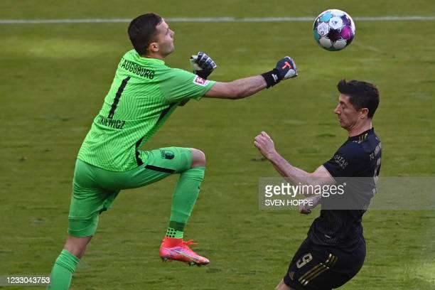 Augsburg's Polish goalkeeper Rafal Gikiewicz and Bayern Munich's Polish forward Robert Lewandowski vie for the ball during the German first division...