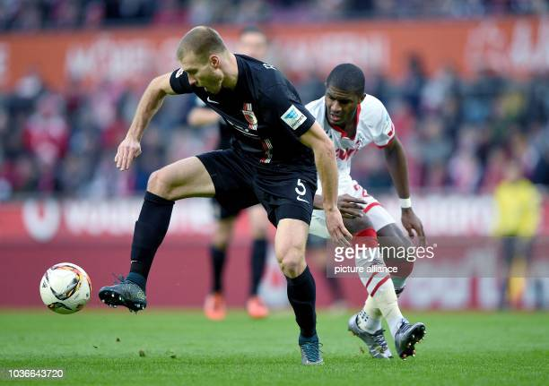 Augsburg's Ragnar Klavan and Cologne's Anthony Modeste compete for the ball during the German Bundesliga football match between 1 FC Cologne and FC...