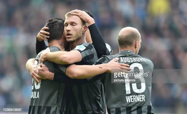 Augsburg's Ragnar Klavan celebrates his 11 goal with Raul Bobadilla Dong Won Ji and Tobias Werner during the German Bundesliga soccer match between...