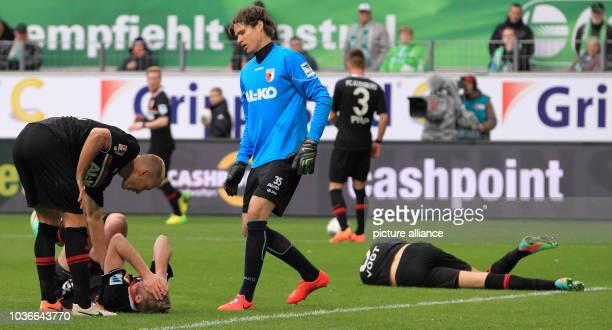Augsburg's Ragnar Klavan JanIngwer CallsenBracker goalkeeper Marwin Hitz Ronny Philp and Kevin Vogt react during the Bundesliga soccer match between...