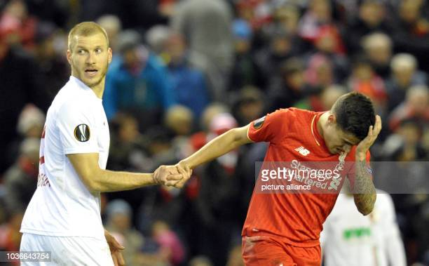 Augsburg's Ragnar Klavan shakes hands with Liverpool's Philippe Coutinho during the UEFA Europa League round of 32 second leg soccer match between...