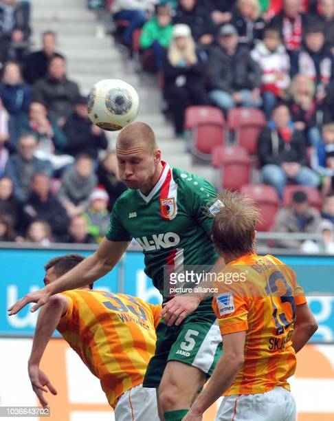 Augsburg's Ragnar Klavan vies for the ball with Berlin's Sandro Wagner and Per Skjelbred during the Bundesliga soccer match between FC Augsburg and...