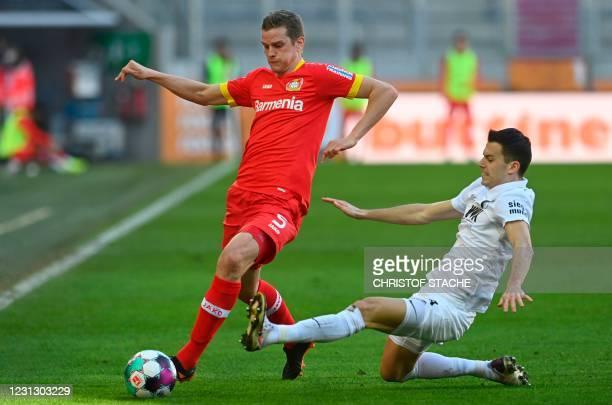 Augsburg's Slovak midfielder Laszlo Benes and Leverkusen's German defender Sven Bender vie for the ball during the German first division Bundesliga...