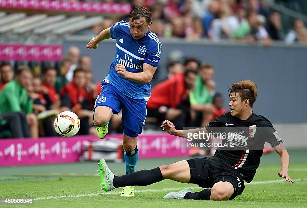 Augsburg's South Korean defender JeongHo Hong and Hamburg's midfielder Ivica Olic vie for the ball during the German Telkom Cup 2015 final football...