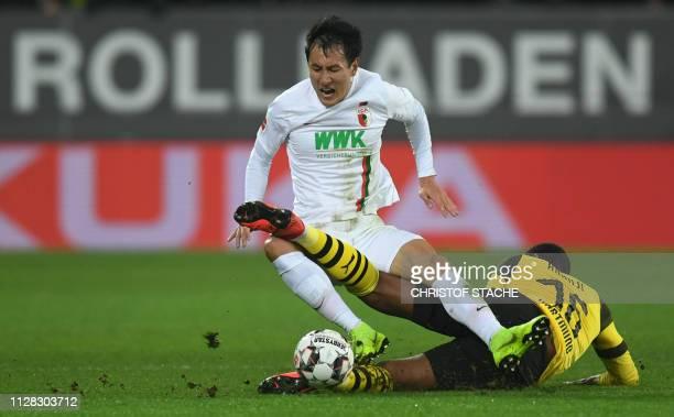 Augsburg's South Korean forward Dongwon Ji and Dortmund's Swiss defender Manuel Akanji vie for the ball during the German first division Bundesliga...