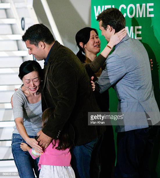August 05, 2009 ––– Euna Lee hugs her husband Michael Seldate and daughter Hanna and Laura Ling hugs her husband Iain Clayton after disembarking the...