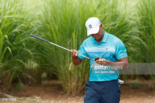 Tiger Woods checks his club after hitting from hard ground during the third round of the Quicken Loans National at Robert Trent Jones Golf Course in...