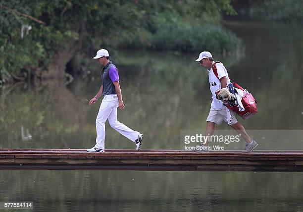 Rory McIlroy and his caddie cross the bridge to tee off on the second hole during the fourth round of the PGA Championship at Valhalla Golf Club in...