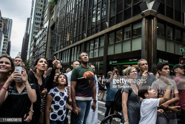 August 10, 2016]: MANDATORY CREDIT Bill Tompkins/Getty Images Spectators watch as a man climbs the glass exterior of the TRUMO Building on August 10,...