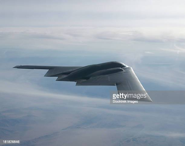august 14, 2003 - a b-2 spirit soars through the sky. - stealth bomber stock photos and pictures