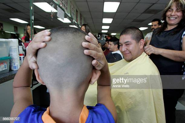 August 16 2008 Carlos Barrera smiles at his son Carlos Jr 5 as he rubs his new fade Every Saturday the two come to Pueblos Unidos hair salon in...