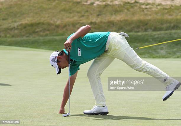 Danny Lee of New Zealand gets his golf ball out of the cup after sinking a putt on the eleventh green during the final round of the PGA Championship...