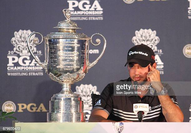 Jason Day, shooting the only 20-under par score in major championship history, sits next to the Wanamaker Trophy and listens to a reporters question...