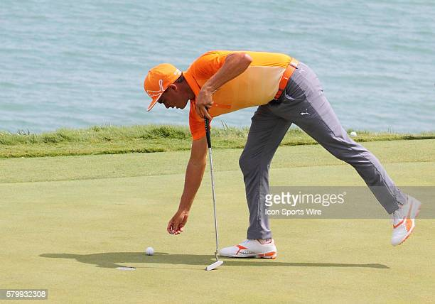 Rickie Fowler bends over to mark his golf ball after nearly scoring a hole in one on number twelve during the final round of the PGA Championship at...