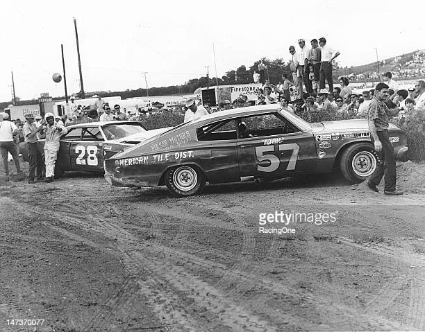 Earl Brooks starts to remove his helmet next to his battered 1966 Ford after he tangled with Ervin Pruitt's 1967 Dodge Charger during the Western...