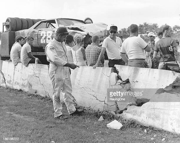 Earl Brooks surveys the damage his Ford did to a wall at AshevilleWeaverville Speedway when he crashed during a NASCAR Cup event Brooks' battered car...