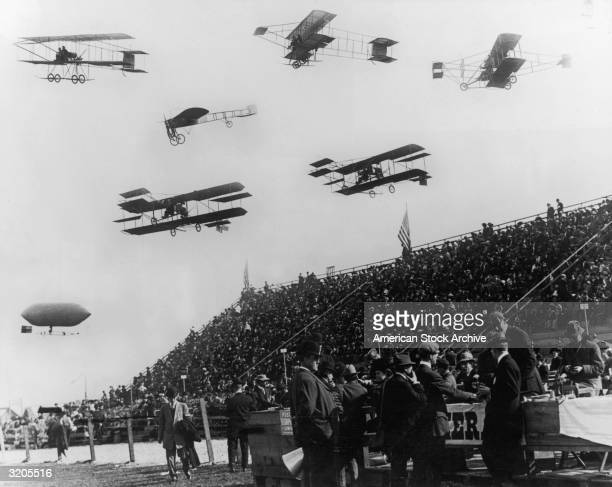 A montage celebrating the Reims 'Aviation Week' air tournament Six participating airplanes and a dirigible fly over the audience Reims France