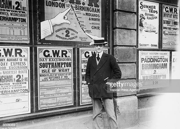 A passenger at Paddington Station poses in front of an array of Great Western Railway posters advertising excursions