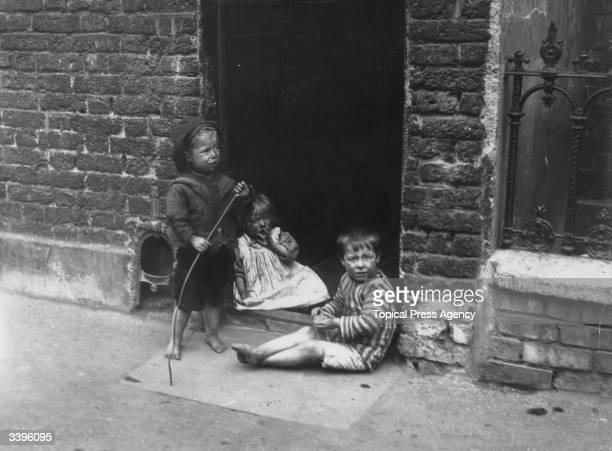 Children sitting in the doorway of their slum home in London