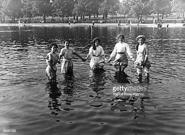 A group of girls have waded into the Serpentine in London's Hyde Park to keep cool during the heatwave