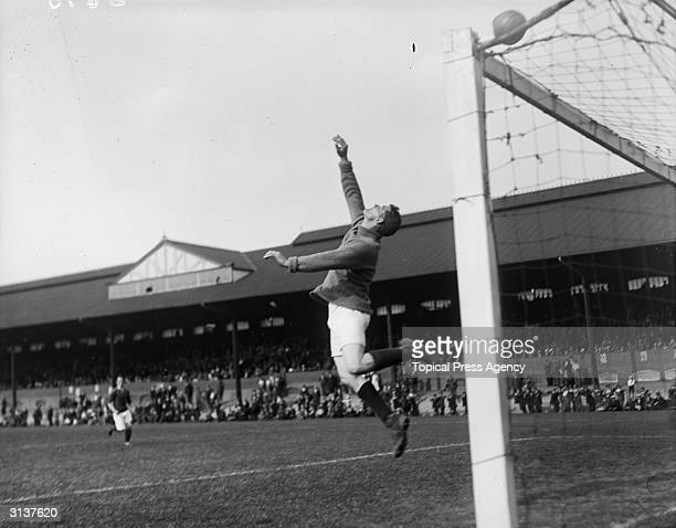 A goalkeeper leaps to deflect the ball during an Army v RAF football match