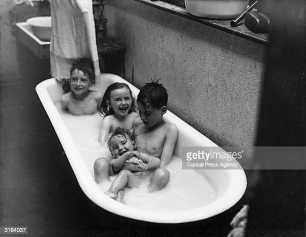 Children cooling off in a bathtub of water during a heatwave