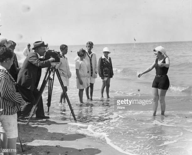 A woman being filmed by cine camera as she paddlles in the sea on a beach at Deauville Calvados France