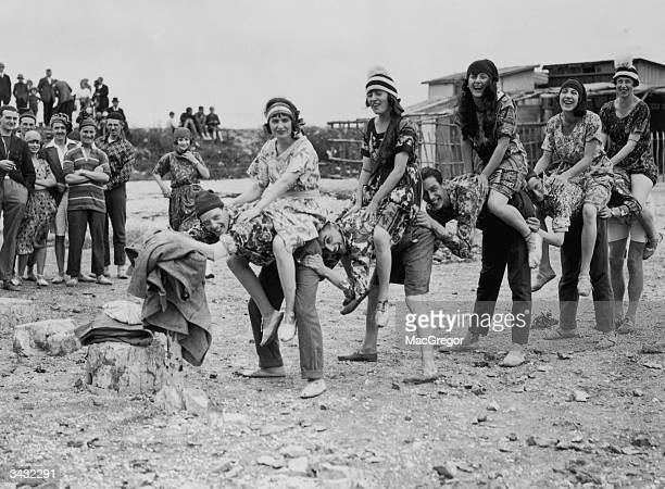 Members of the Cretonne Club wearing cretonne shirts and dresses made of heavy cotton with a floral design playing leapfrog at Canvey Island in Essex