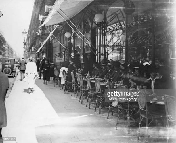 People sitting and drinking outside the Cafe la Rotunda in a busy Paris street