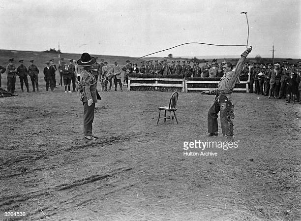 Two men demonstrate the art of the lasso at a rodeo at Aldershot.