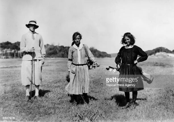 Edward, Prince of Wales playing golf in Le Touquet, France accompanied by two girl caddies.